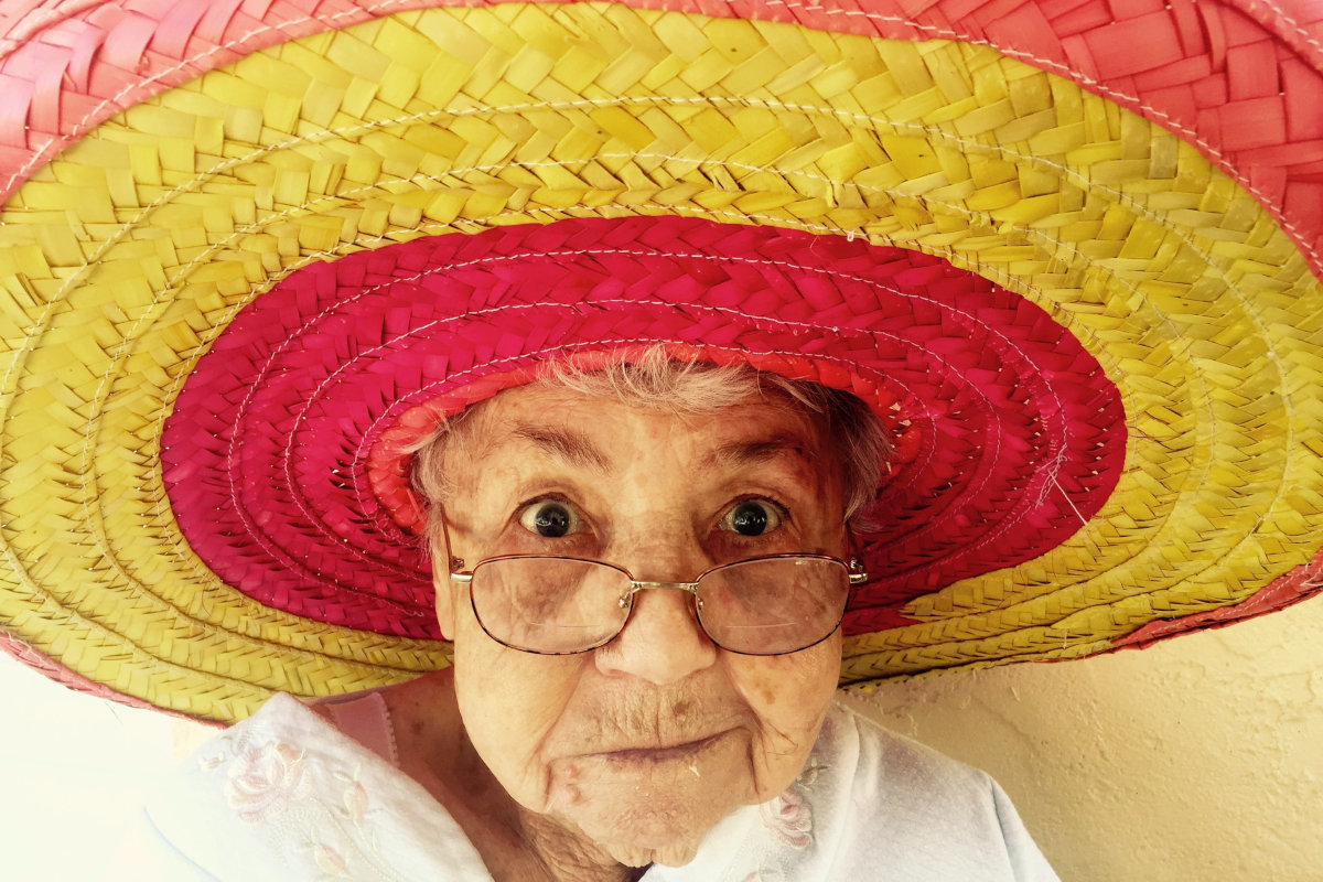 old woman wearing red and yellow straw hat