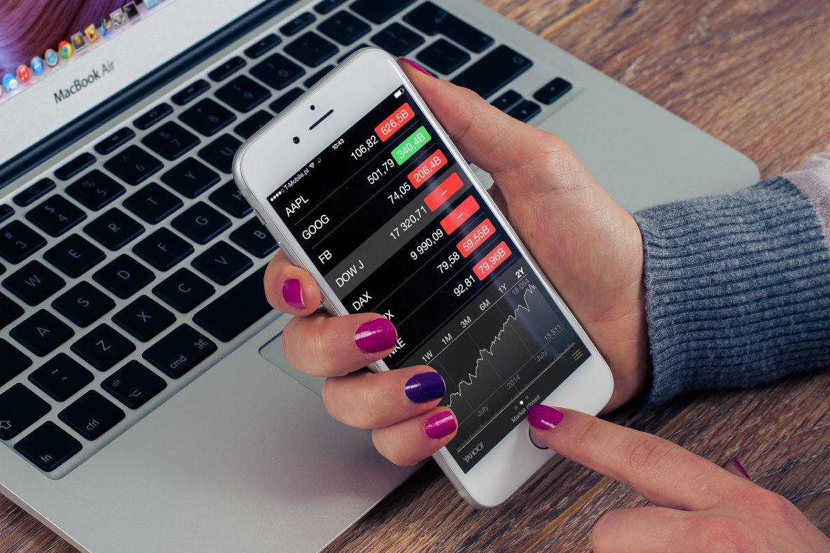 woman with pink nails checking stock information on phone