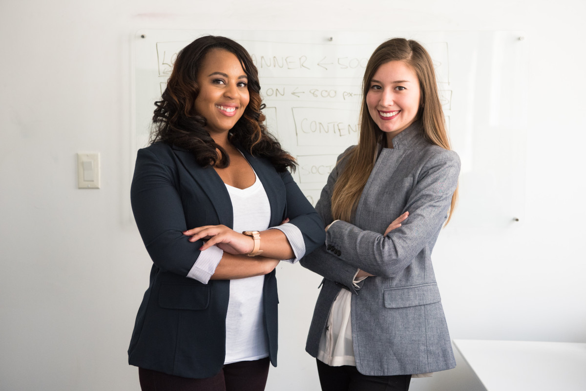 Two business women standing next each other with folded armes