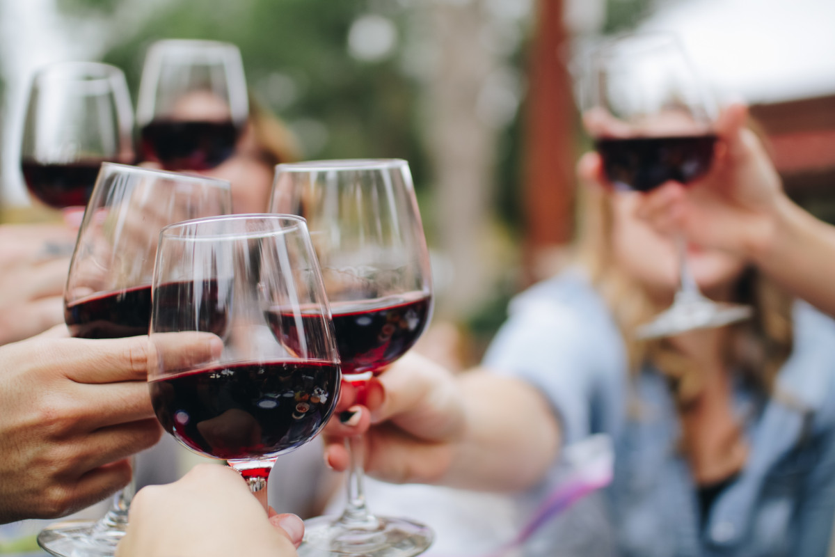 People cheering with red wine
